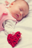 Little baby with heart shape toy Royalty Free Stock Image