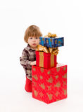 Little baby hiding behind presents Royalty Free Stock Photos
