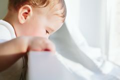 Little baby holds onto the bed and looks somewhere. Royalty Free Stock Photo