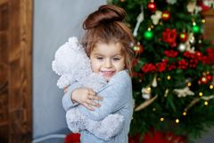 A little baby hugs a beaded toy. The concept of Christmas and Ne Royalty Free Stock Photo