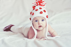 Little baby with knitted white hat. Pretty baby with knitted white hat lying on the white covered bed Stock Images
