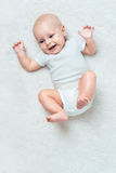 Little baby is laughing on the carpet Stock Image