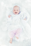 Little baby laughing. Laughing little girl 6 months in a white shirt on white cloth Stock Photography