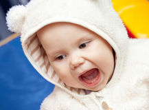 Little baby laughs with open mouth. In white bear costume Stock Photography