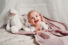 A little baby lays on a bed with a toy rabbit and smiles royalty free stock photos