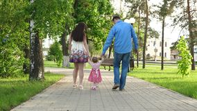 Little baby learning how to walk with mom and dad,happy family walking in summer Park. Little baby learning how to walk with mom and dad helping him to make his royalty free stock images