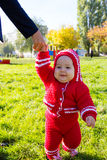 Little baby learning to walk. Mom holding baby's hand Royalty Free Stock Photography