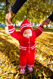 Little baby learning to walk. Mom holding the baby's hands Stock Images