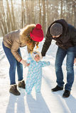 Little baby learning to walk. Mother and father with toddler boy at the winter park Royalty Free Stock Photography