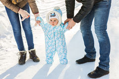 Little baby learning to walk. Mother and father with toddler boy at the winter park Stock Photos