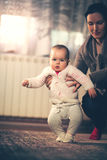 Little baby learning to walk with mother help at home Stock Image