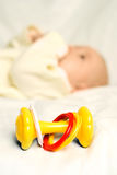 Little baby lies on the bed with a toy Royalty Free Stock Photo