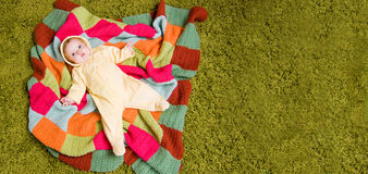 Little baby lies on colorful blanket Royalty Free Stock Photos