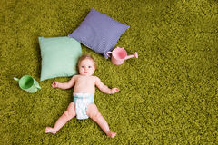 Little baby lies on green carpet Stock Photos