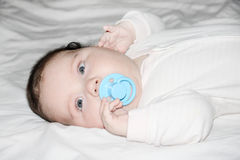Little baby lies on white sheet on bed Stock Photos
