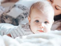Little baby looking at camera, mother unfocused stock images