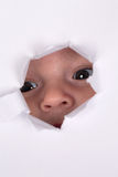 Little Baby looking through a hole, curiosity topic Royalty Free Stock Image