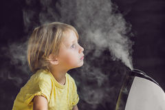 Little baby looks at the humidifier. Moisture in the house concept Stock Image