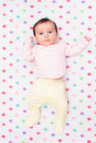Little baby lying on blanket with colourful polka dots Royalty Free Stock Photos