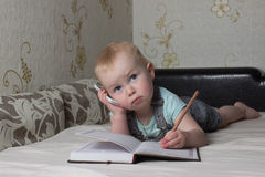 little baby lying on the couch and writing in a notebook pen Royalty Free Stock Photo