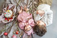 Baby lying on linen blanket and wearing a hat in the form of a Easter bunny with her brother near eggs willow branches royalty free stock images