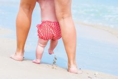Little baby making the first steps. With mother by the sea shore Stock Images
