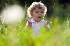 Little baby in the midle of green nature Stock Photo