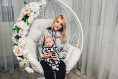 a little baby with mom on her hands on a round swing smiles Stock Images
