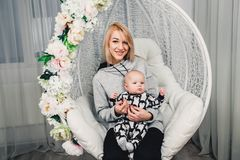 a little baby with mom on her hands on a round swing smiles Stock Photos