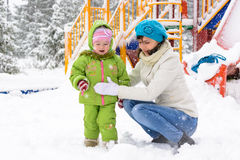 Little baby and mother are playing with first snow Stock Photos