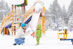 Little baby and mother are playing with first snow Stock Photo