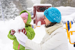 Little baby and mother are playing with first snow Stock Photography