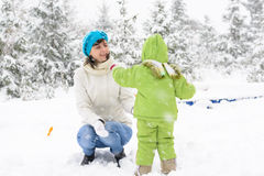 Little baby and mother are playing with first snow Stock Image
