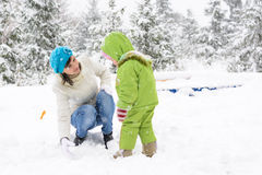 Little baby and mother are playing with first snow Royalty Free Stock Photo