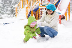 Little baby and mother are playing with first snow Royalty Free Stock Image