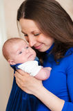 Little baby in mother's arms Stock Images