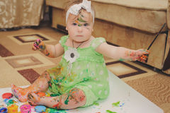 Little baby paint by her hands at a home. Royalty Free Stock Photo