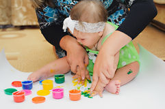Little baby paint by her hands at a home with mother. Stock Photography