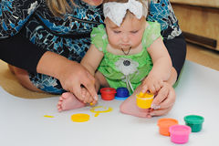 Little baby paint by her hands at a home with mother. Stock Photos