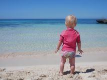 Little baby in pink swimming suit looking at the aquamarine blue see from a sand beach royalty free stock image