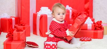 Little baby play near pile of wrapped red gift boxes. Gifts for child first christmas. My first christmas. Sharing joy. Of baby first christmas with family royalty free stock photo