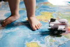 A little baby playing with an aircraft toy on the world map, close up legs, travel with children royalty free stock photography