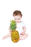 Little baby playing with a big pineapple stock image