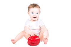 Little baby playing with a big red paprika Royalty Free Stock Photo