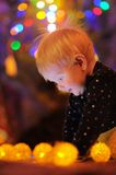 Little baby playing by a Christmas tree Royalty Free Stock Images