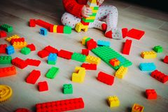 Little baby playing with colorful plastic blocks. Early learning stock image