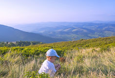 Little baby playing with grass in the mountains in summer. Baby boy sitting in the grass. Beautiful mountains landscape Stock Photo