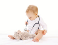 Little baby playing and listens stethoscope Royalty Free Stock Photo
