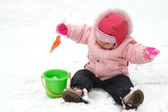 Little Baby Playing on Snow with Rabbler. Little Baby Playing with Snow in Winter Outdoors Royalty Free Stock Image