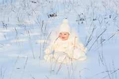 Little baby playing in a snowy winter field Royalty Free Stock Photography